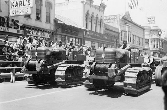 """Tractors in a parade down Main Street, Watsonville.  Date: ca. 1948  Place: Watsonville  Sources of Information: Notes on back of photo; Signs in photo; Directory  Original Size: 3"""" x 2""""  Medium: b  C/O Santa Cruz Public Library"""