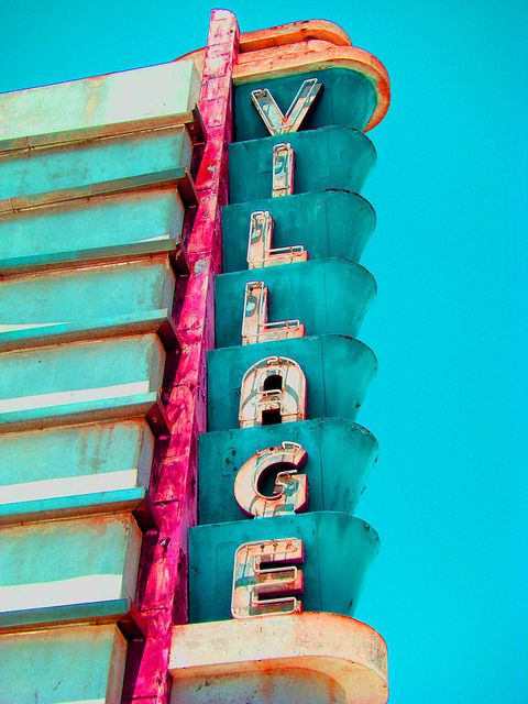 """.Bright, color-drenched vintage neon cinema theater sign entitled """"It takes a Village."""" This charming midcentury, theatre sign spells it out, complete with its rusty edges. The theater, located in California is now closed."""
