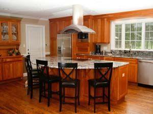A stylish range hood hangs over an island with a built in - Kitchen island with cooktop and seating ...