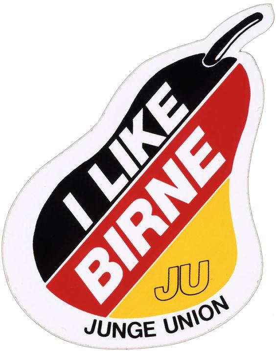 Birnenförmig-unregelmäßig geformter Aufkleber; Grundfarbe der Birne: schwarz-rot-gelb; weiße Aufschrift.