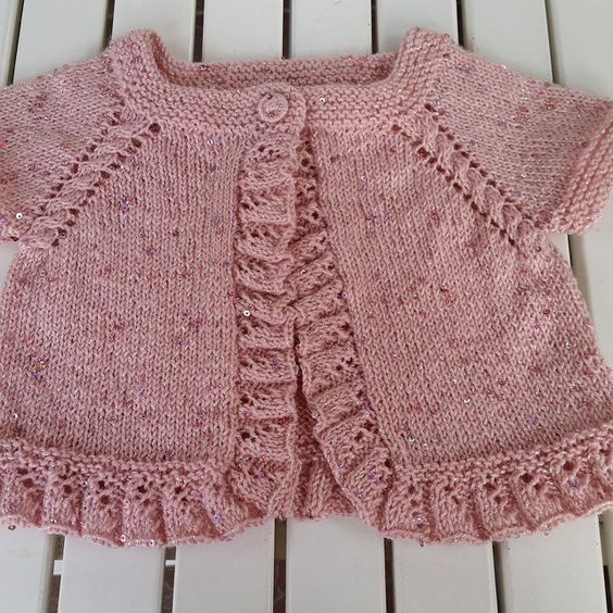 Pretty top-down pattern with cable on raglan line (increases at each side of cable) and sweet ruffles on front edges and hem. Lovely shade of pink, too.: