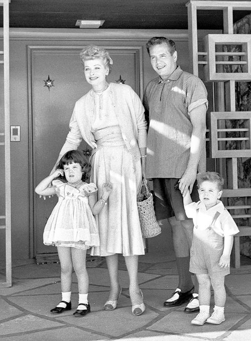 Lucille Ball and Desi Arnaz photographed outside their home with their children, 1954
