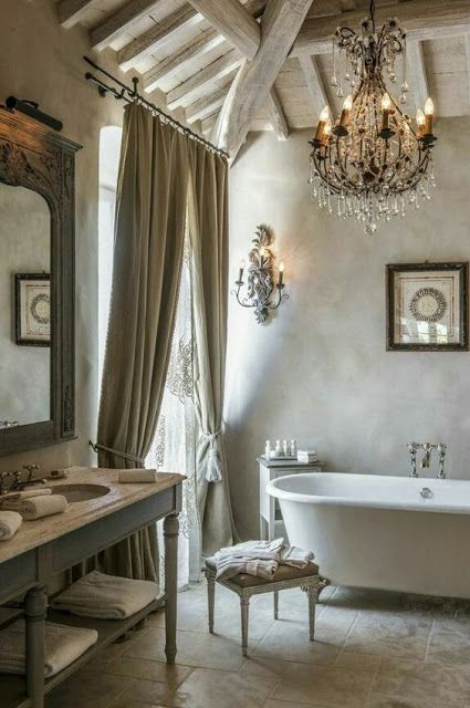 French Country bathroom decor in an elegant French farmhouse with crystal chandelier and clawfoot tub. The Venetian plaster walls are stunning! #bathroomdesign #bathroomdecor #frenchfarmhouse #frenchcountry #interiordesign #decorideas #oldworld #crystalchandelier #clawfoottub