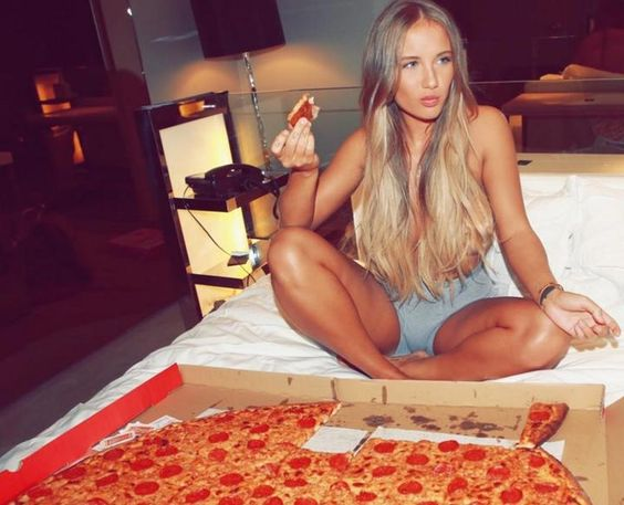 Singer Niykee Heaton eating pizza in bed after a concert