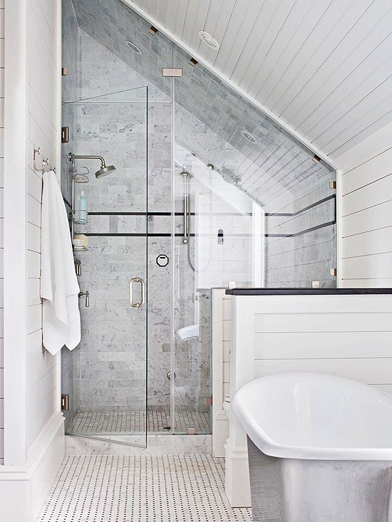This spacious shower includes multiple showerheads and a pleasing mix of white, gray, and black tile