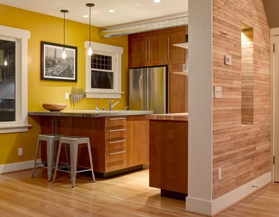 Vivid colors, like this bright sunny tone, inject much-needed warmth into small kitchens. Project completed by NEST Design Build  - GoodHousekeeping.com