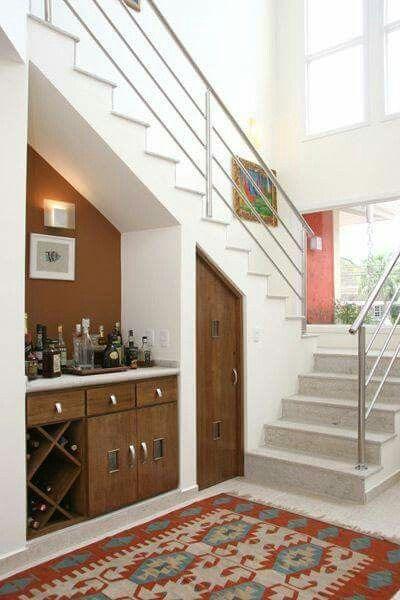 Um bar embaixo da escada aproveitamento o espaço.