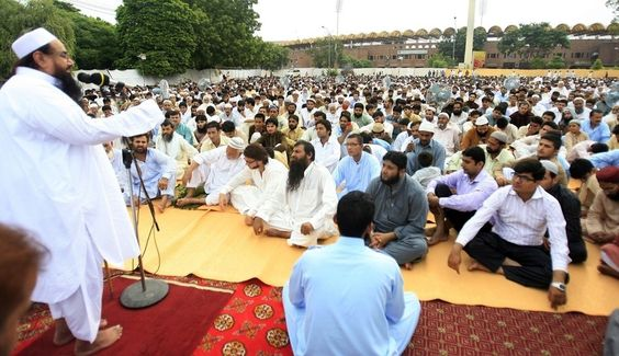 """Incredibly Powerful Images Of Eid Al-Fitr 2013, And What They Say About The World Today...Lahore, Pakistan...Hafiz Mohammad Saeed (L), leader of the banned Lashkar-e-Taiba militant group with suspected links to the 2008 terror attacks in Mumbai,India, delivers his sermon after Eid al-Fitr prayers at the Gaddafi stadium in Lahore.  He tweeted: """"Time is near when those oppressed in Kashmir, Palestine and Burma will celebrate 'Eid' in the air of Freedom - Insha'Allah."""""""