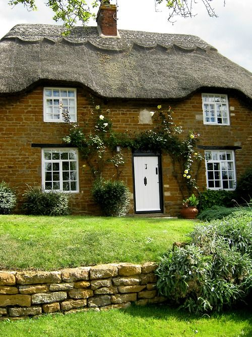Thatched cottoage with white door and windows. Preston, Rutland, England, UK