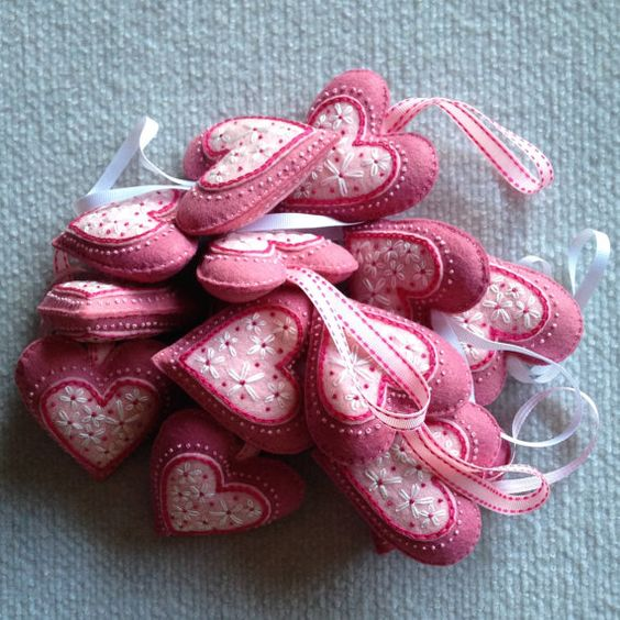 Adorno de corazón hecho de rosa rosa, rosa rosada y caliente fieltro rosa. Corazón adornado con una gran cantidad de mano de costura en hilo color