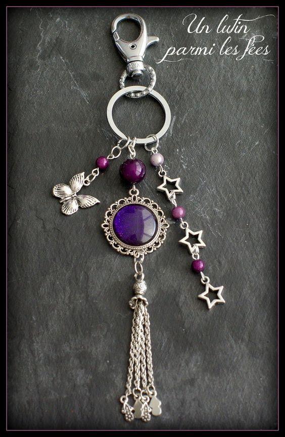 Bijou de sac ou porte clé cabochon couleur violet pailleté, breloque papillon, pompon argenté et étoiles