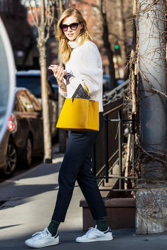 Karlie Kloss wears a ribbed turtleneck sweater, cropped trousers, gray socks, Adidas sneakers, and a top-handle yellow Louis Vuitton bag: