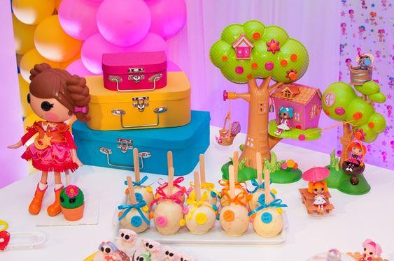 Decoração de mesa com elementos do desenho Lalaloopsy, malas decorativas e maçãs decoradas