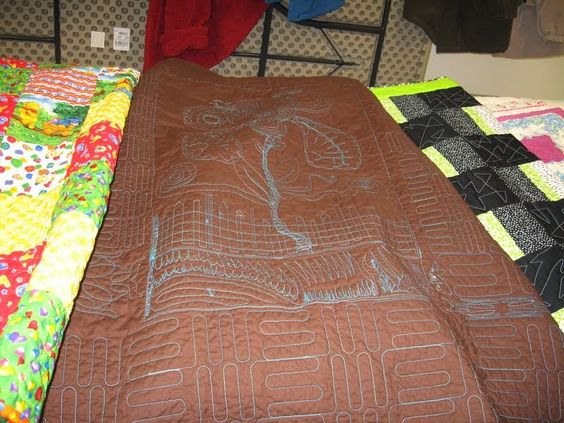 Back of a quilt that I quilted with computer and FMQ.  To the left is another quilt I completed from a UFO -- B.