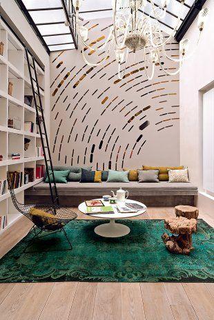 salon contemporain avec banquette en béton ciré, table basse d'Eero Saarinen (Knoll) et sur un des murs une  fresque de Françoise Doléac en tôles d'inox poli découpées au laser reflète