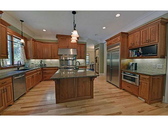 Kitchen - Rustic Cherry Cabinets with a natural finish.  Stainless Appliances, Granite counters, Hickory Flooring.  Designs of Home - designsofhome.com