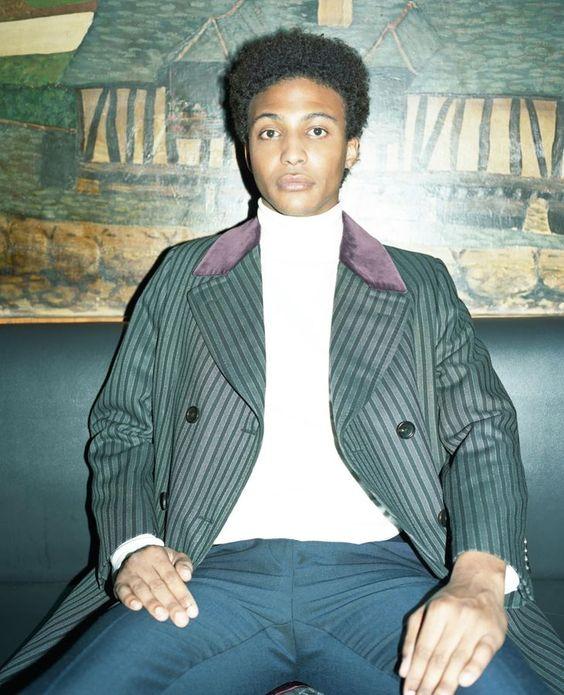 Moussa : manteau en laine rayée à col de velours, Gucci. Pull col roulé en jersey de coton, Sandro. Pantalon en laine, Fendi.