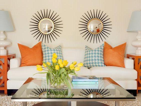 checked pillows, pop of orange, modern sunburst mirrors