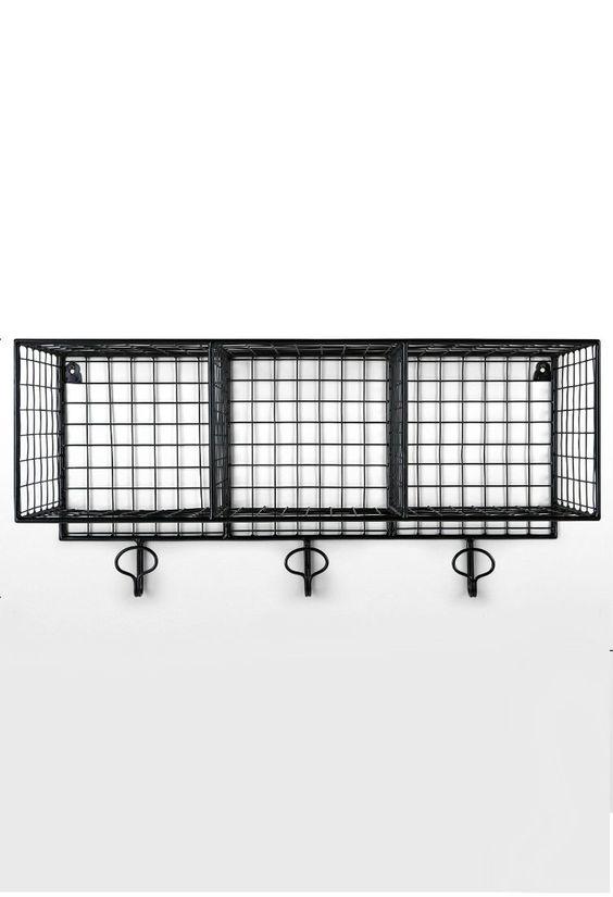 Amph Wandschrank mit Stauraum in Schwarz. Die Amph Metallregale erinnern an klassische Hängekörbe. Wir haben sie aber veredelt und mit praktischen Fächern und Haken ausgestattet. Erhältlich in Schwarz oder Kupfer – äußerst fotogen.