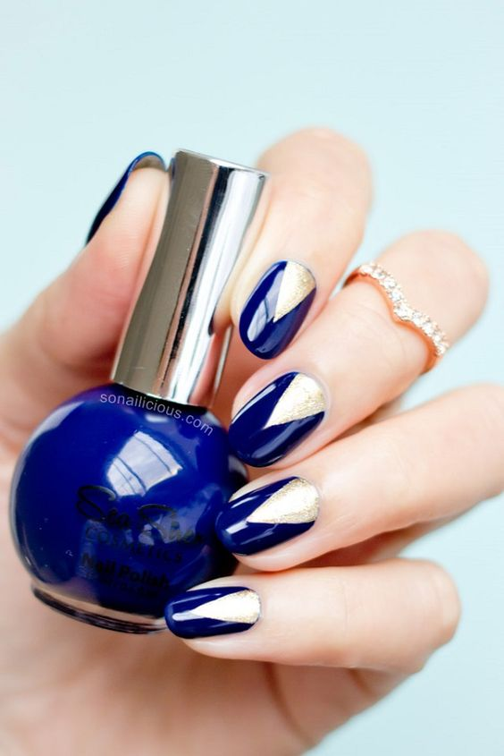Beautiful v-shaped dark blue nail art design. The nails have a dark blue polish background d and are topped with white nail polish in v-shapes.