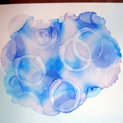 Copic ink is dripped onto paper. Dip a cardboard tube into sanitizer gel, which because it has alcohol in it, will make the ink run when the tube is pressed onto the paper.