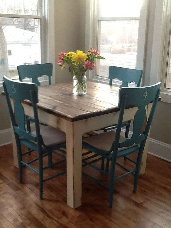 love this quaint square table with wood finish top offset with white distress...and finished with the dark turquoise chairs. Perfect for a little cottage kitchen.