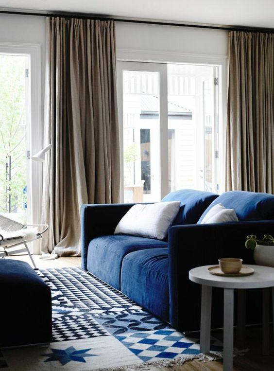 rideau en lin, un sofa bleu et beau tapis géométrique
