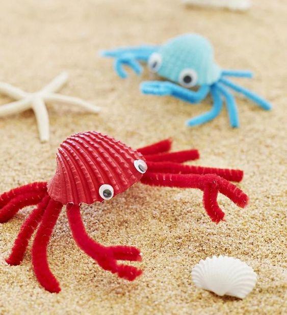 activité manuelle primaire, coquilles de mer colorées avec des pinces en cure pipe colorée sur sable