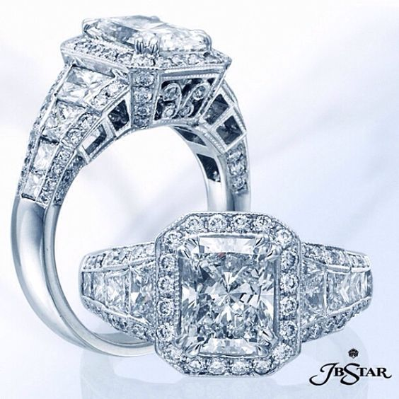 Beautifully crafted this engagement ring features a radiant diamond center with radiant diamond sides and pavé edging.