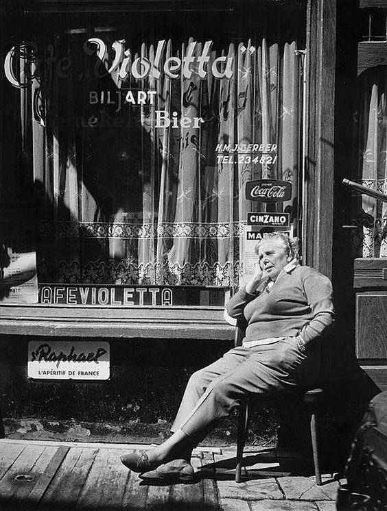 1966. Bet van Beeren in front of café Violetta across the street from her café 't Mandje at the Zeedijk in Amsterdam. 't Mandje is considered to be the first gay bar in the Netherlands and one of the first in the world. It was opened in 1927 by Bet, herself a lesbian. After her death in 1967 her sister Greet operated the café until 1983. In 2008 the cafe was reopened again by family members. Photo Sam Presser. #amsterdam #1960 #Mandje #Zeedijk #BetvanBeeren