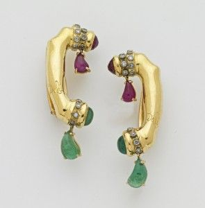 """Dali's telephone ear-rings. Schiaparelli commissioned Dali's earliest  jewelry, including this earrings. His sub-title for these earrings was """"The persistence of sound."""" He wrote, describing these earrings, """"The ear is a symbol of harmony and unity; the telephone design a reminder of the speed of modern communication – the hope and danger of instantaneous exchange of thought"""". These are in 18k gold, with rubies, emeralds and diamonds."""