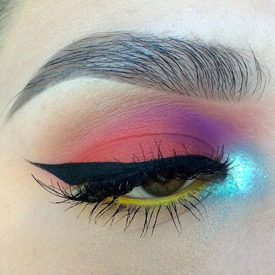 Pink, purple, shimmery blue, and yellow eye shadow with winged black eye liner.: