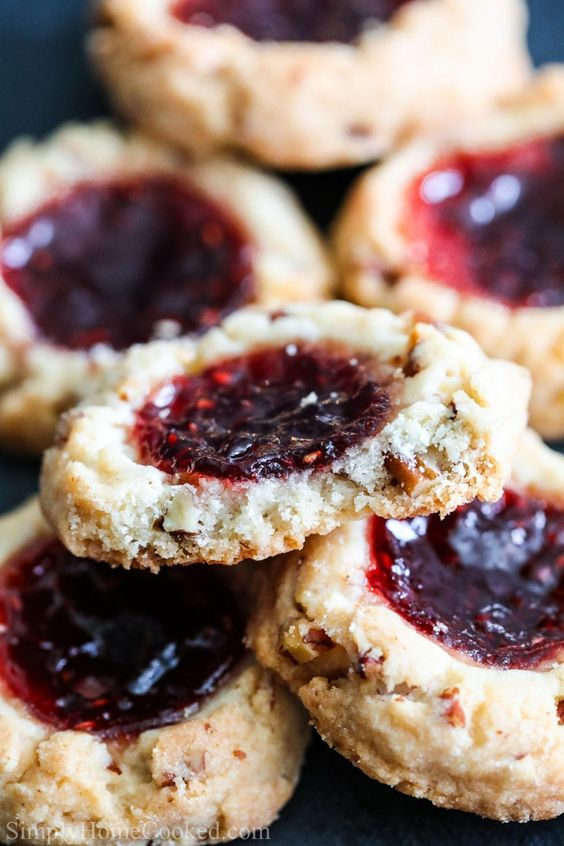 These raspberrythumbprint cookies are loaded with toasted pecans and raspberry jam. Every bitejust crumbles and melts in your mouth. #thumbprintcookies #jamdropcookies #raspberrycookies #jamcookies #christmascookies