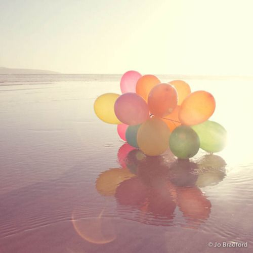 colorful balloons on the beach-  looks like a dream
