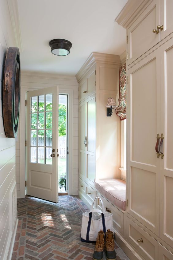 A neutral Mudroom with brick herringbone floors, and cabinetry painted in Oat straw by Benjamin Moore #MUDROOM
