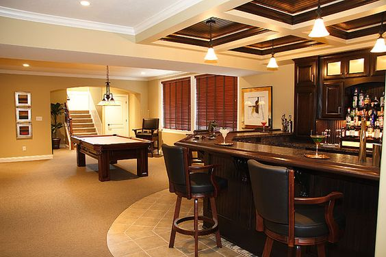 Traditional dark wood bar and games area are the essential pieces for the ultimate man cave. Would you be interested in upgrading your unfinished basement into something like this?