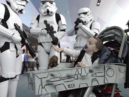Samwise, Sharknado and more at Cincinnati Comic Expo. Photo: Thomas Wells, 2, from Hamilton as Han Solo aboard The Millennium Falcon, actually his stroller, seems unaware of the presence of Storm Troopers from the same Star Was adventure. Costumes were on display at the Cincinnati Comic Expo at Duke Energy Center downtown. The Enquirer/Michael E. Keating