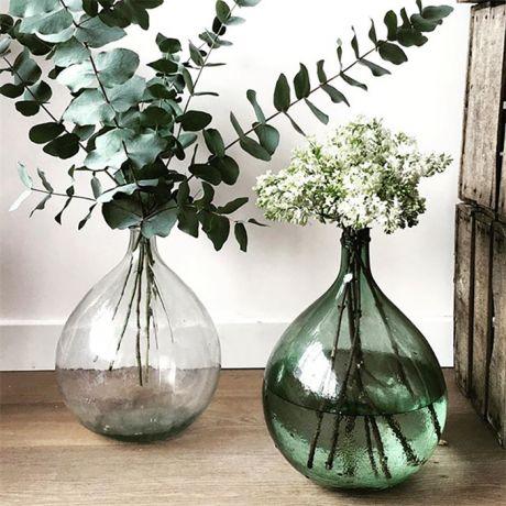 Fleurs disposées dans des Dames Jeanne blanche et verte