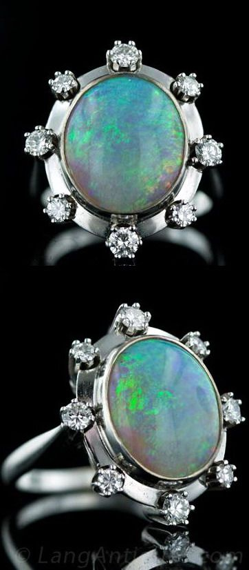Estate Opal and Diamond Ring. 14k, white gold mounting features a vibrant 6 carat opal with flashes of green, blue, violet and red. The opal is bezel-set and surrounded with a high polished frame containing 0.75 carats of evenly spaced prong-set brilliant-cut diamonds.