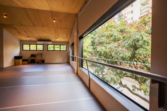O concreto aparente na fachada equilibra as cores do exterior e valoriza as esquadrias desalinhadas. Piso de cimento queimado, paredes de tijolinho, telha metálica e teto revestido com chapas de compensado dão aconchego. Nas salas, a estrutura metálica foi mantida e restaurada para agregar valor ao conceito industrial aplicado ao projeto, remetendo os antigos galpões e lofts nova-iorquinos. #arquitetura #architecture #interiors #design #window #janela #concreto #concrete #industrial