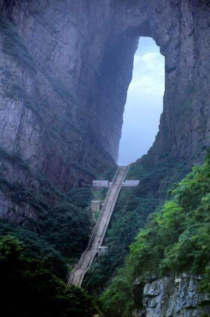 "Heaven's Gate Mountain, Zhangjiajie City, China - Years ago, a cliff collapsed here and left a 400ft-tall hole, which many now believe to be the door to heaven. This staircase leading to the hole consists of 999 steps, the number ""9"" being chosen because it has the same pronunciation as the word for ""eternal"" in Mandarin."