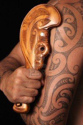 Close up of maori tamoko tribal tattoo and carved wooden mere club