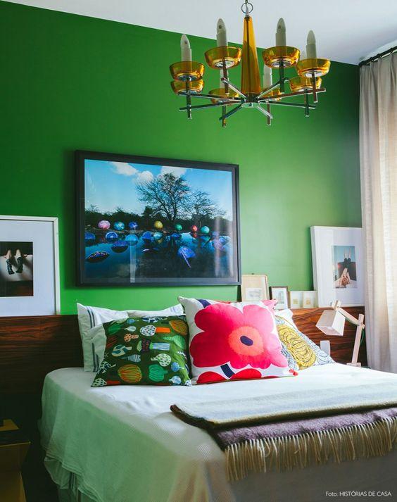 Quarto com parede verde bandeira, lustre antigo e almofadas coloridas da marca Marimekko.