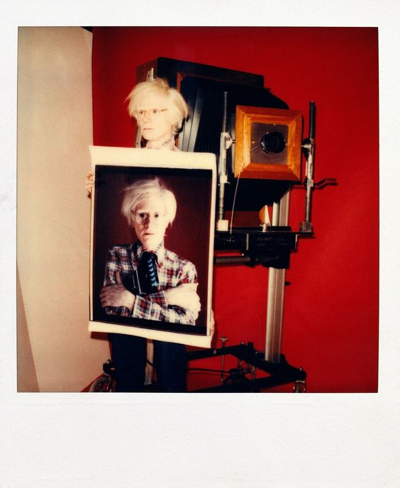 Andy Warhol with large format Polaroid camera and Self-Portrait photograph, 1976 (Polaroid)  © The Andy Warhol Foundation for the Visual Arts, Inc.|