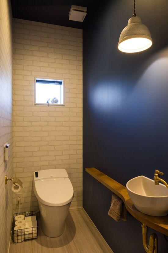トイレ ネイビーのアクセントクロスが映えるトイレ 手洗器や照明に