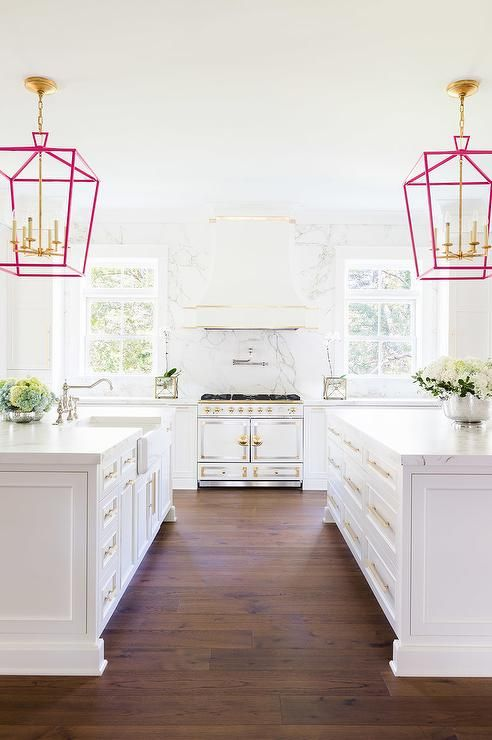 Laura Burleson Interiors - White and gold kitchen features white cabinets adorned with long gold pulls paired with Silestone quartz countertops and backsplash that look white marble.: