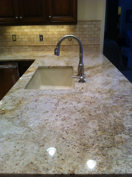 The calacatta gold granite in this kitchen matches well with the tiles on the backsplash. It also creates a little bit lighter accent for the dark brown cupboards.
