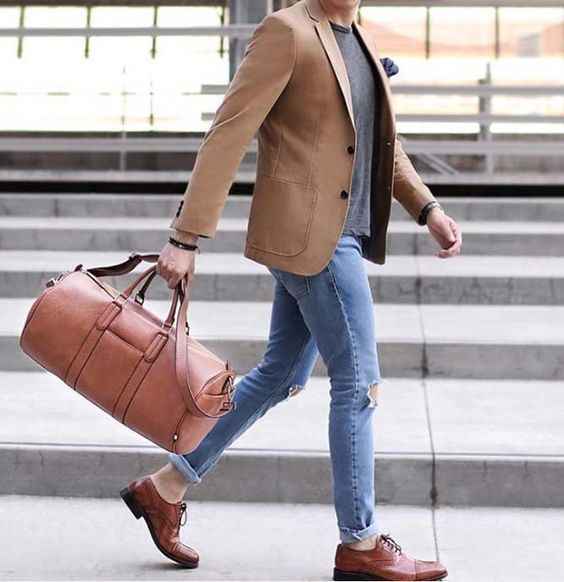 This combination of a tan coat and baby blue destroyed skinny jeans is perfect for a night out or smart-casual occasions. A pair of brown leather oxford shoes will bring a strong and masculine feel to any ensemble. Shop this look on Lookastic: https://lookastic.com/men/looks/blazer-crew-neck-t-shirt-skinny-jeans/22255 — Tan Blazer — Navy Pocket Square — Grey Crew-neck T-shirt — Light Blue Ripped Skinny Jeans — Tan Leather Holdall — Brown Leather Oxford Shoes #ad