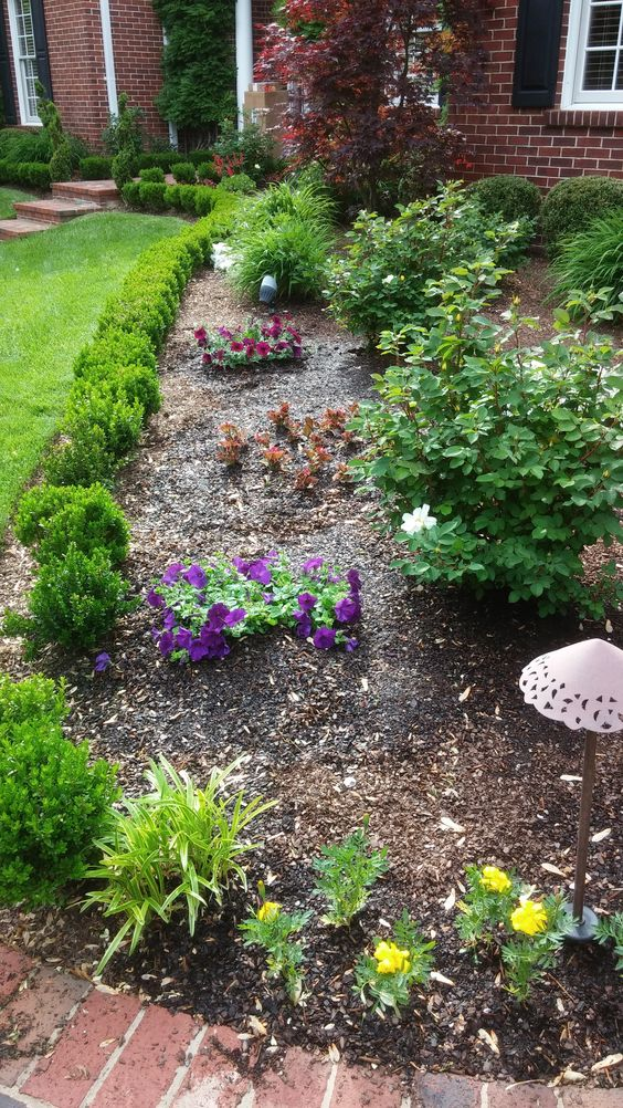 Clusters of colorful annuals provide splashes of seasonal interest in open spaces without detracting from the formal planting scheme. Petunias, begonias, and marigolds are used here.