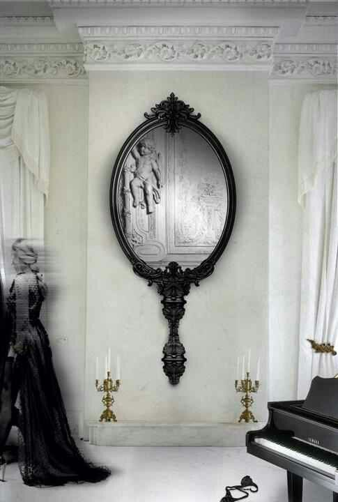Gothic style mirror. Its a wall hung mirror that looks like a portable mirror used in the 16-18th century, the handle element is highly decorated.:
